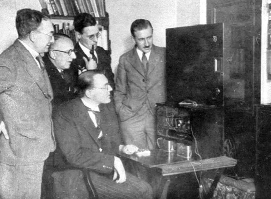 HJ Barton-Chapple (seated) giving the first demonstration of television in Bradford from the BBC London station - taken in Sidney R. Wright's house in Nab Wood, 8 October 1929.  Also in the photograph are Sydney Moseley (left), and Mr. Wright (one of the two younger men).