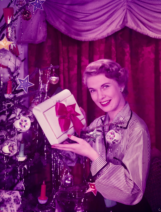 Glamorous woman holds present beside Christmas tree, c.1950, Photographic Advertising Limited © National Media Museum, Bradford / SSPL. Creative Commons BY-NC-SA