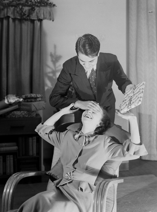 Man surprising a woman with a Christmas present, c.1950, Photographic Advertising Limited © National Media Museum, Bradford / SSPL. Creative Commons BY-NC-SA