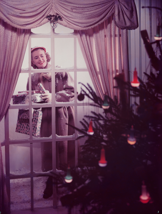 Woman looking through a window at a Christmas tree, c.1950, Photographic Advertising Limited © National Media Museum, Bradford / SSPL. Creative Commons BY-NC-SA